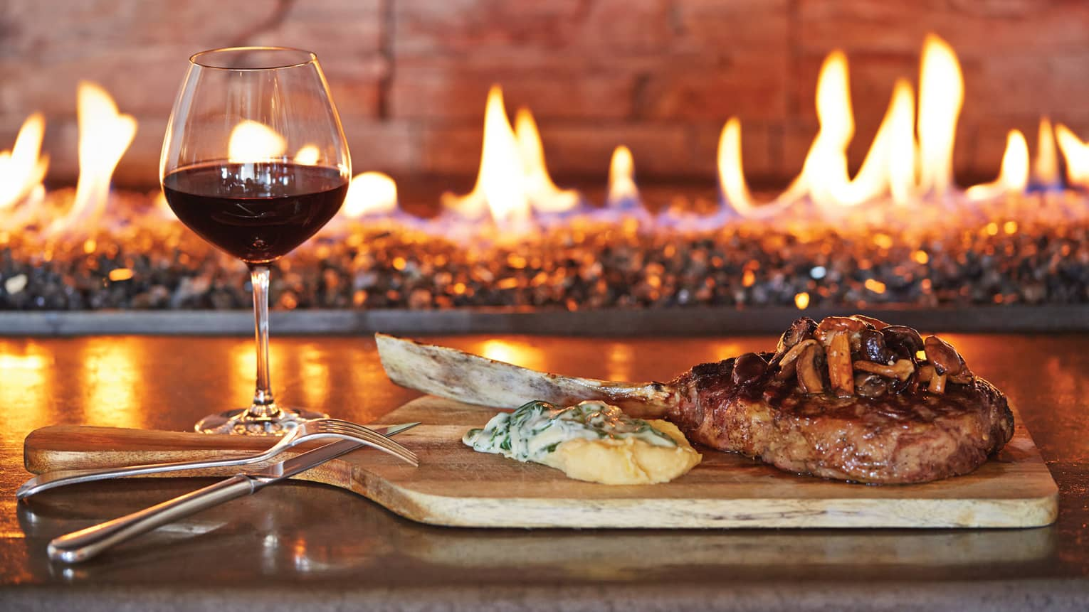 Glass of red wine, grilled chop on wood platter with cheese, mushrooms by fireplace