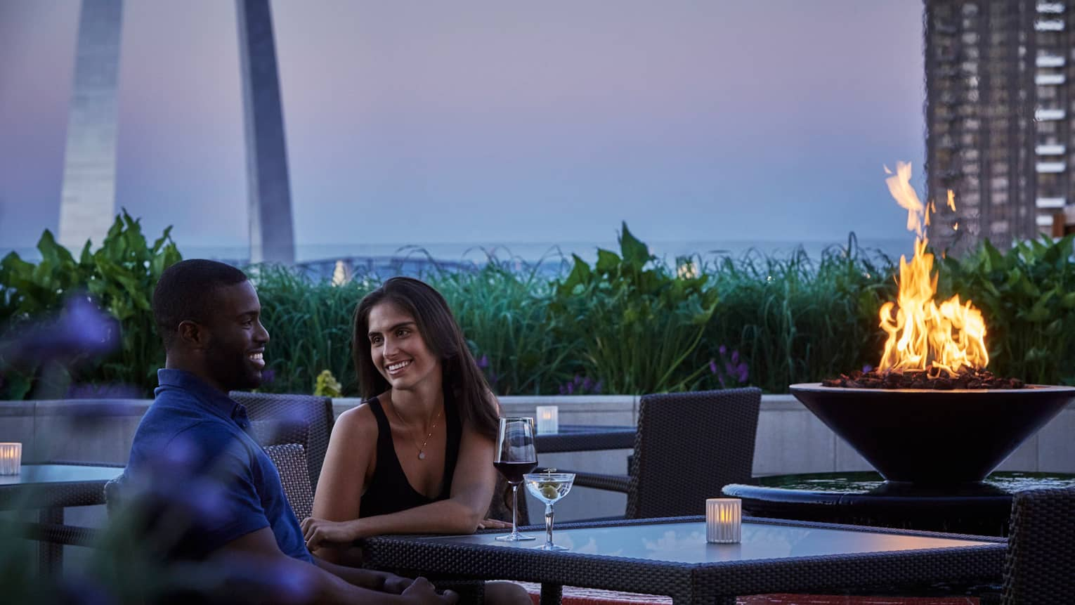 Smiling man and woman with martini and wine sit at rooftop patio table at dusk, near outdoor fireplace