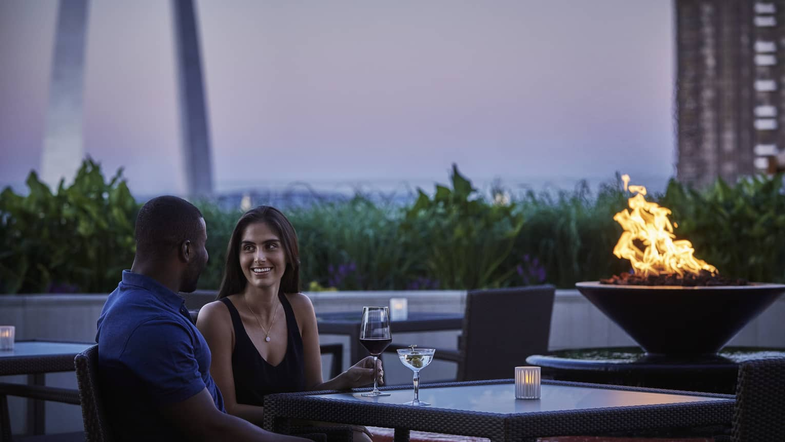 Smiling man and woman with wine glass and martini beside outdoor fireplace at dusk