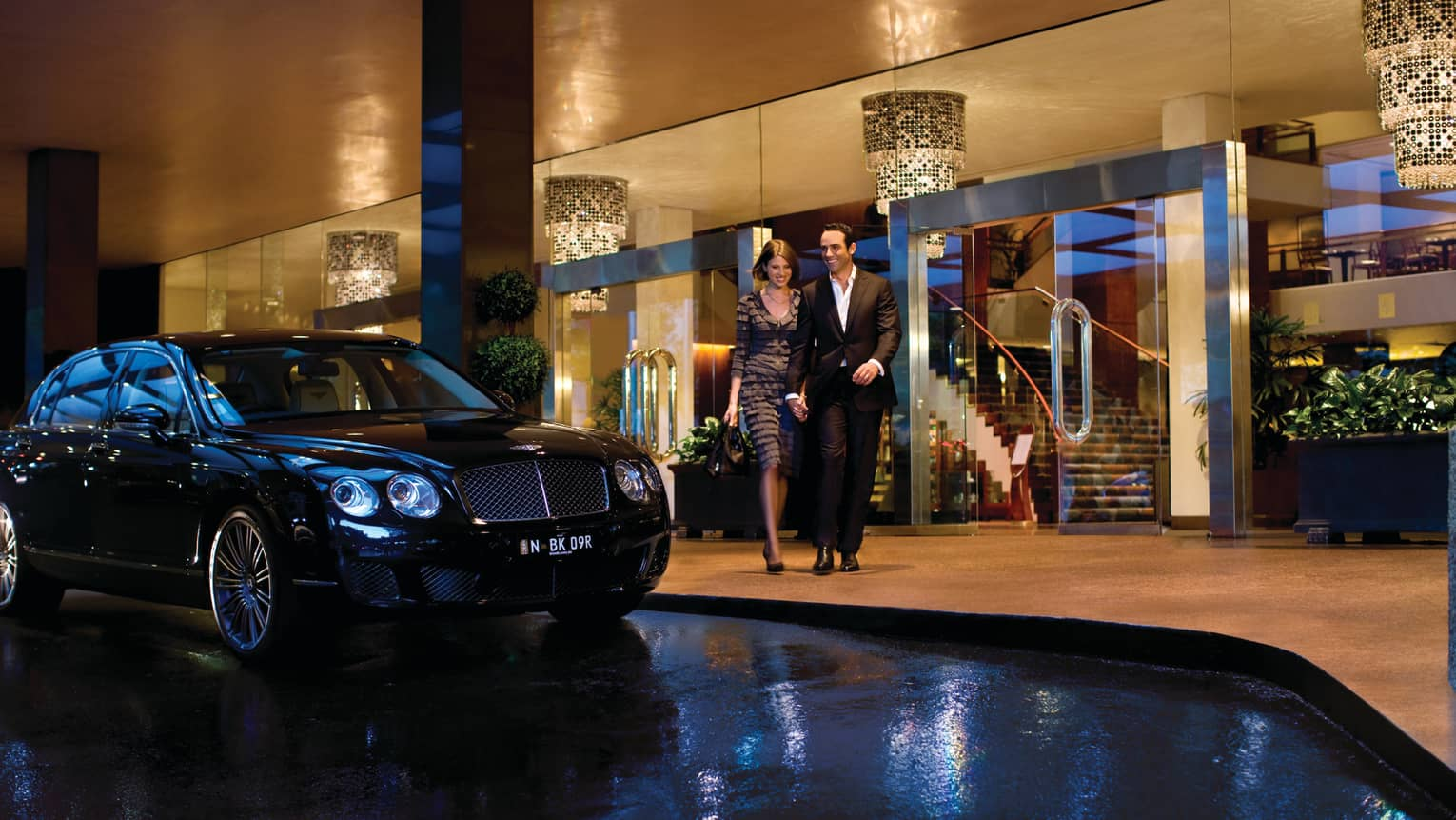 Man and woman walk arm-in-arm past luxury car, Four Seasons Hotel Sydney entrance