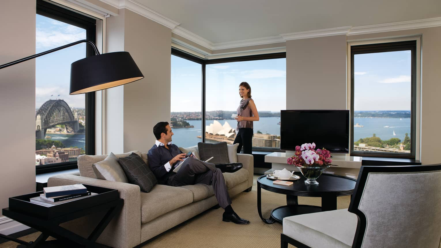 Presidential Suite, woman stands at corner windows, man reads magazine on sofa