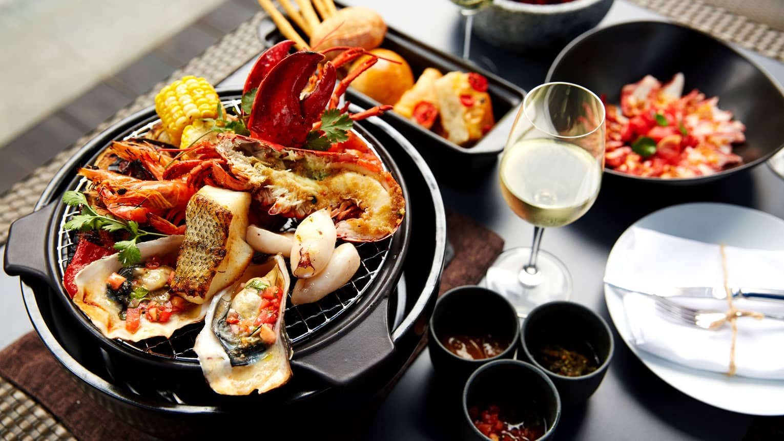 Grilled fish, oysters, lobster, crab on grill plate next to white wine, garnishes
