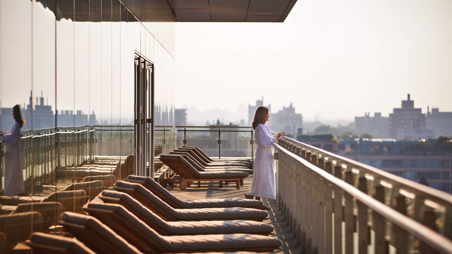 Woman in white bathrobe looks out over balcony ledge near row of spa patio chairs