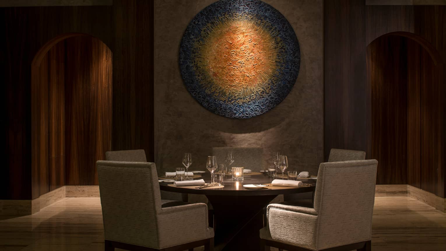 The Creek restaurant dining table, chairs under modern round art sculpture in dimly-lit room