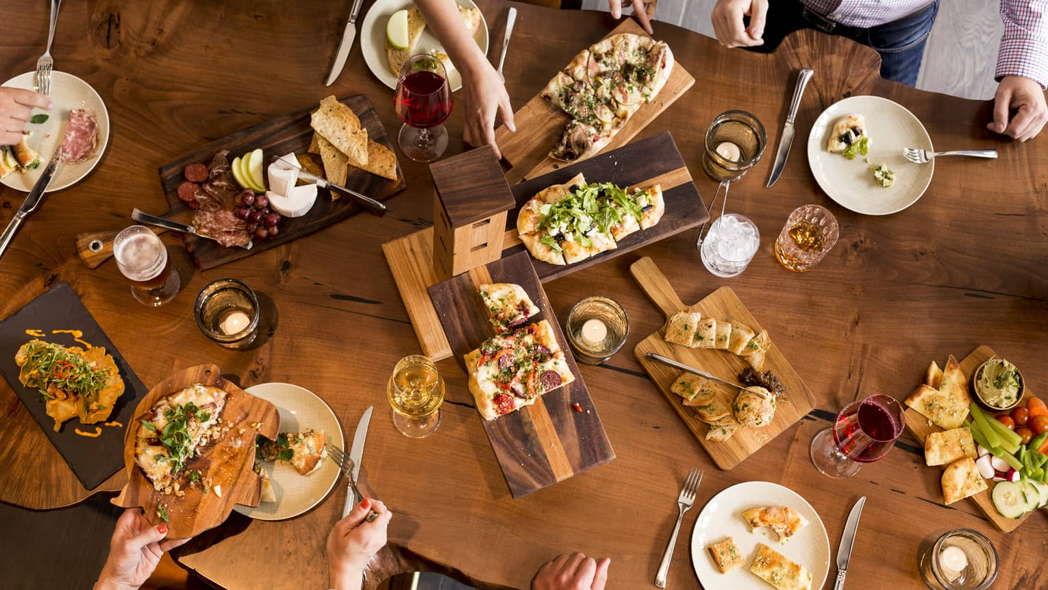 Aerial view of people dining around rustic wood table with platters of flatbreads, appetizers