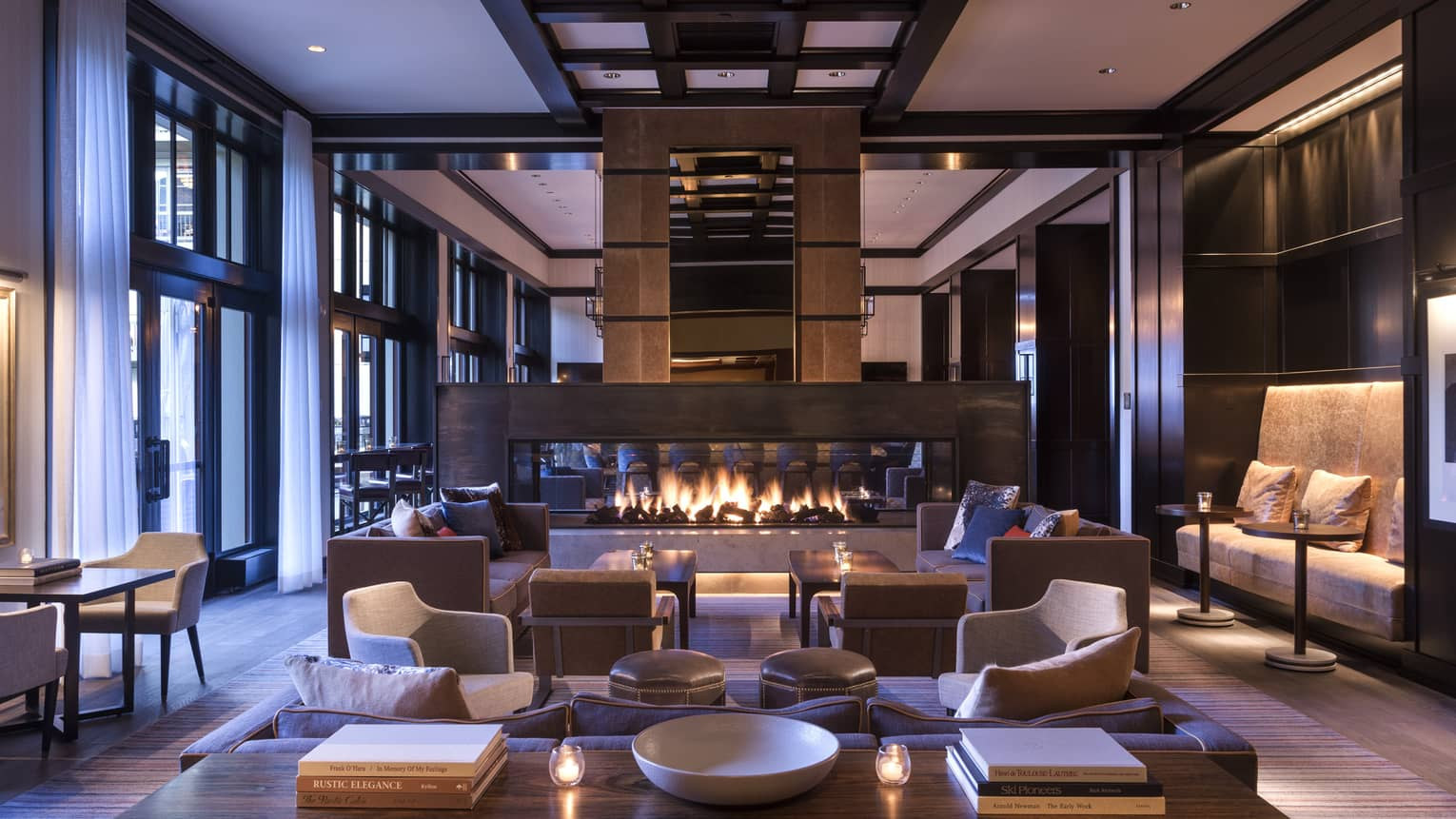 Indoor bar and lounge with a sofa, arm chairs and long fireplace