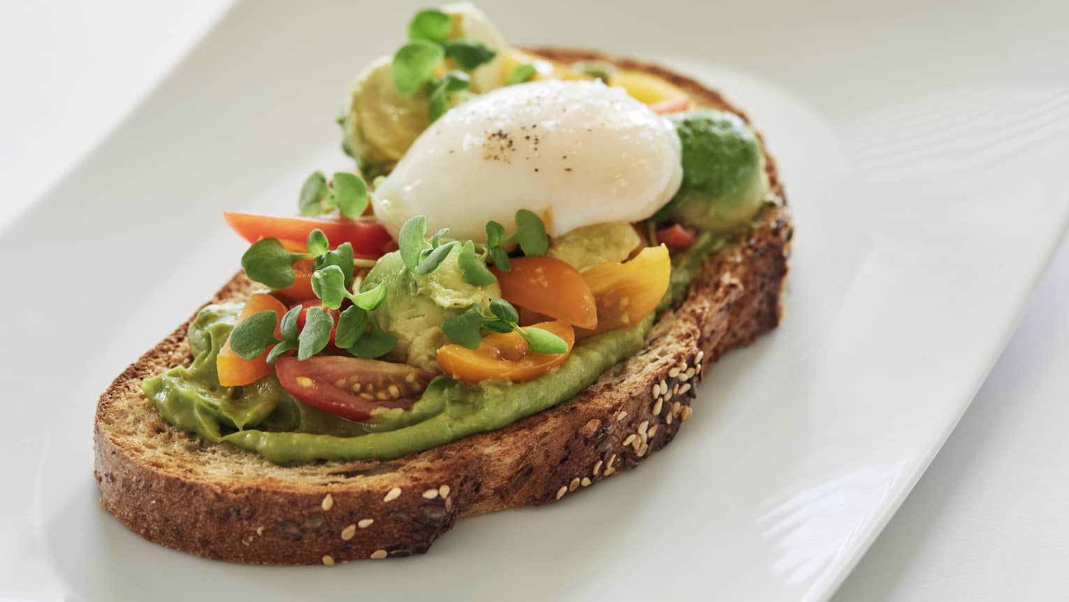 Avocado toast with cherry tomatoes, sprouts, poached egg