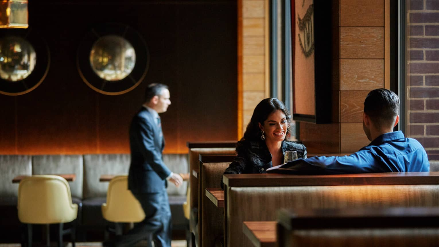 Smiling woman and man in booth in The Lounge at BOURBON STEAK dining room, man in suit walks in background