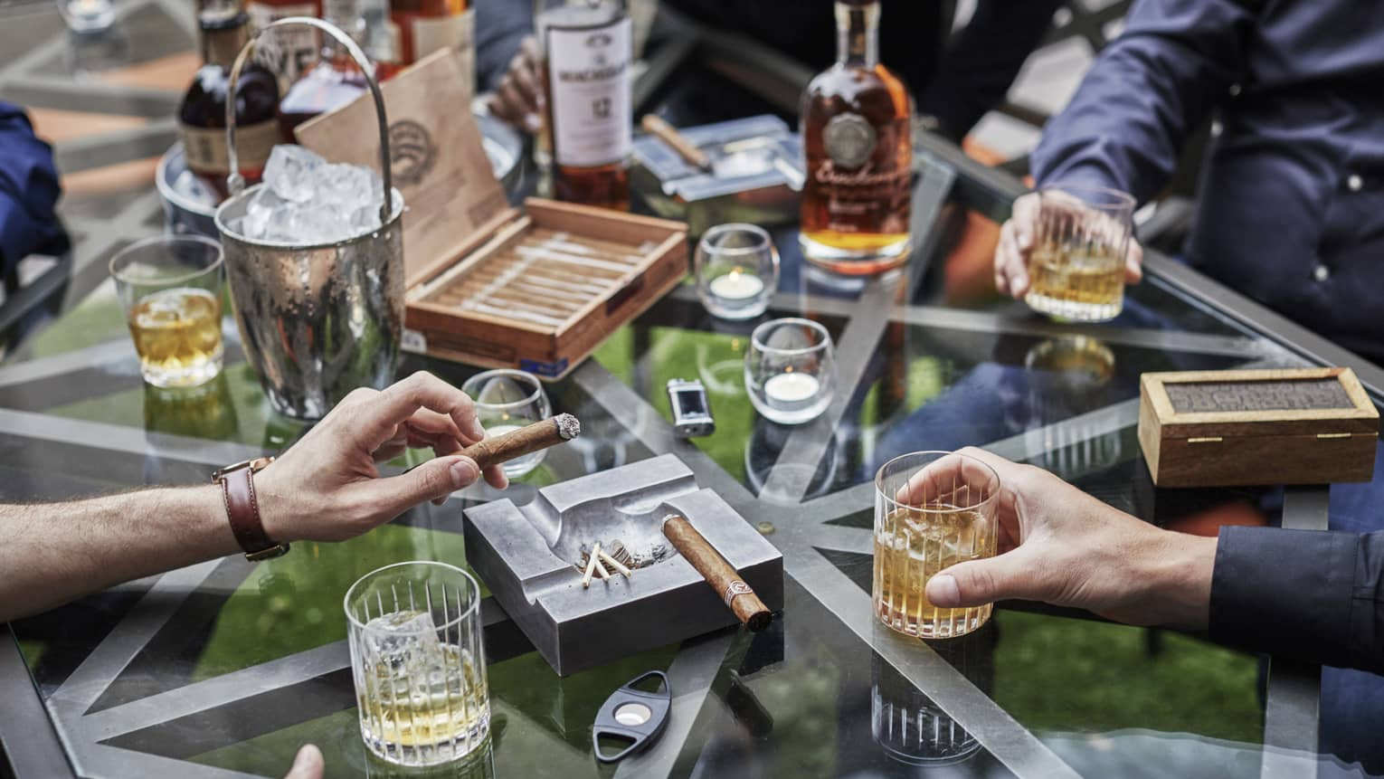 Bachelor party scene with men's hands holding rock glasses with liquor and thick cigars at glass table