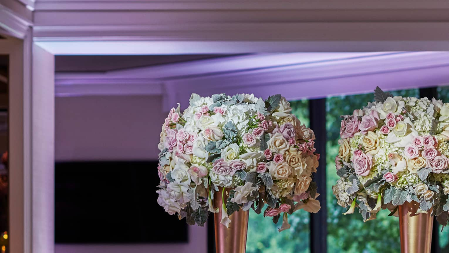 Four tall floral centrepieces in rose gold vases, candles on long wedding banquet table