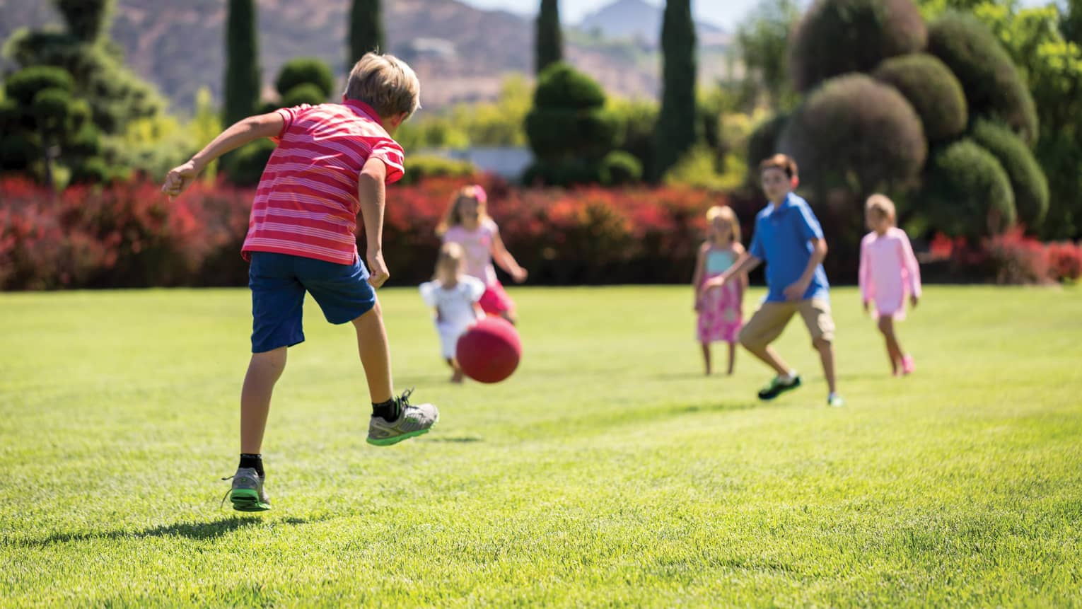 Kids playing with a ball on green grass outside.