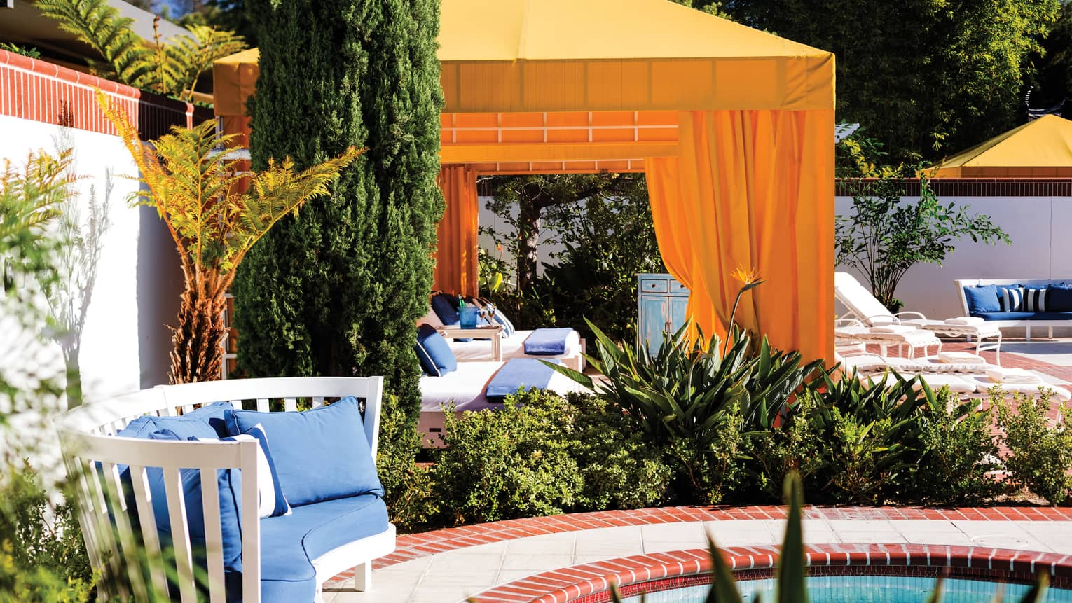 Yellow cabanas, trees on red brick patio by plush blue bench, outdoor swimming pool
