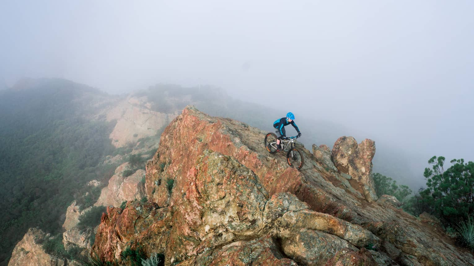 Cyclist rides down large boulder at top of misty mountain