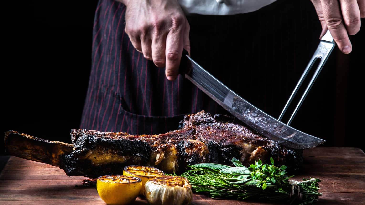 Close-up of chef slicing large rack of grilled meat, vegetables with butcher knives