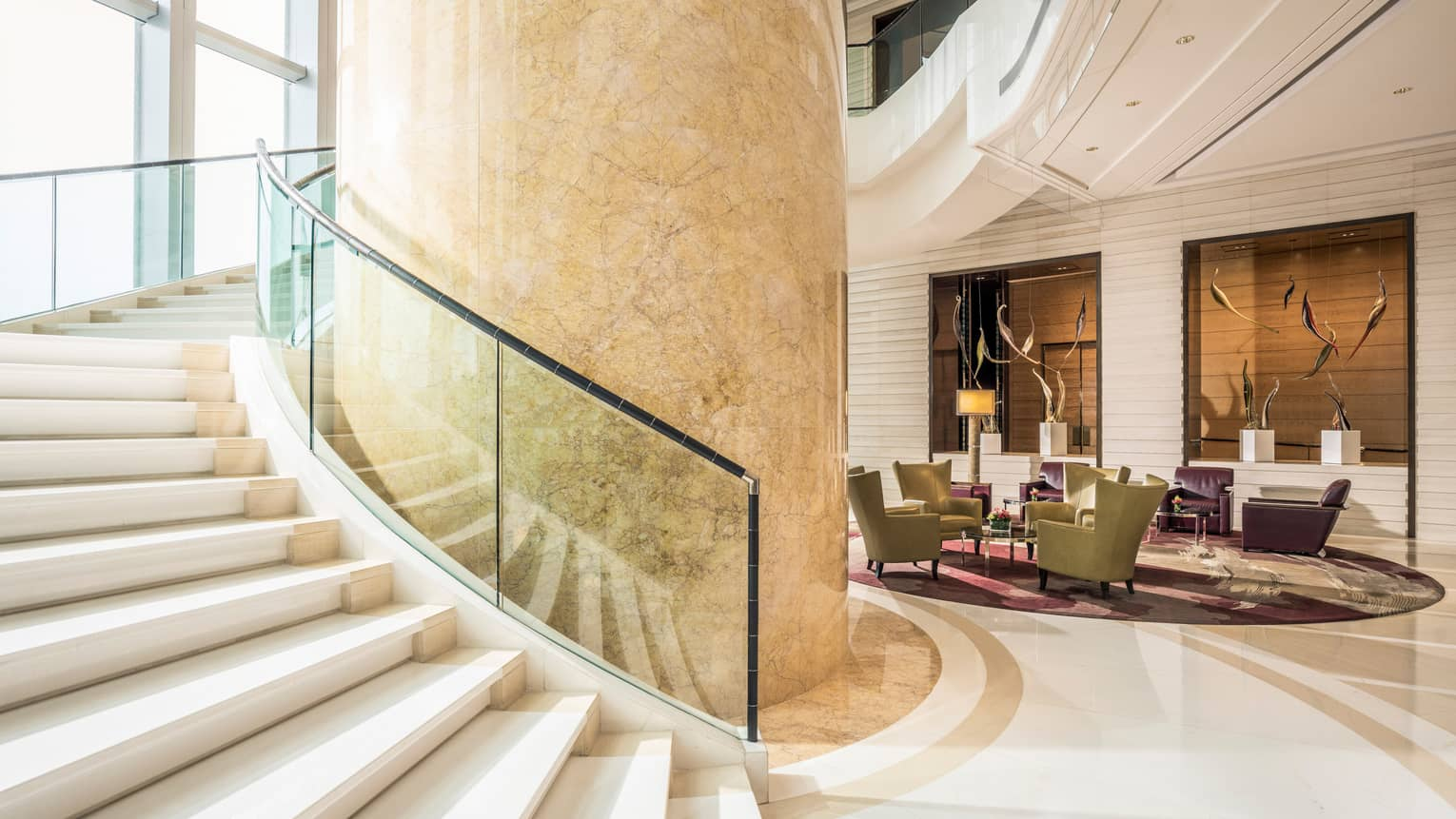 Large beige marble pillar, sweeping staircase with glass balcony in Four Seasons Hotel Hong Kong lobby