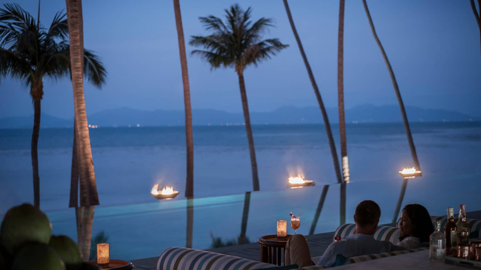 CoCoRum patrons look out at tall palm trees, outdoor fireplace line infinity pool in front of ocean at night