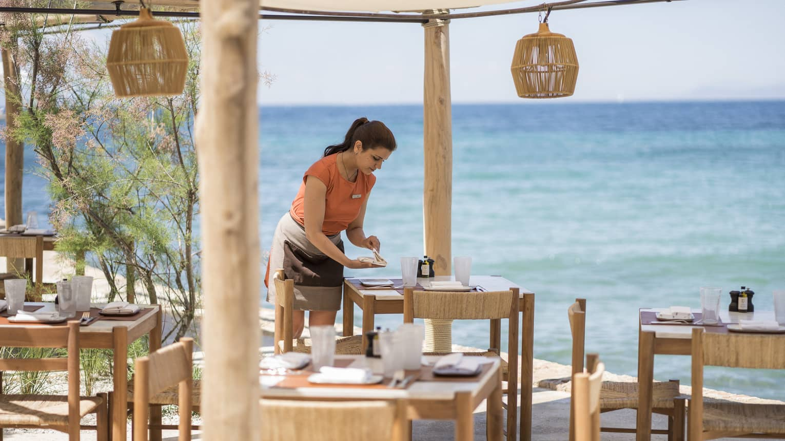Woman in orange top sets wooden table at outdoor Taverna with wooden lanterns by ocean