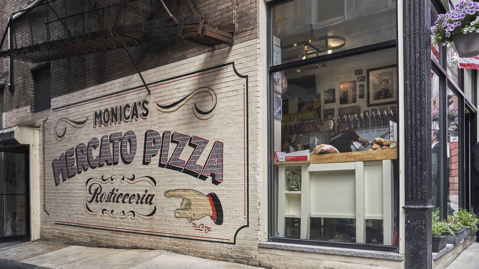 "white Brick mural on the side of a corner restaurant that reads, ""Monica's Mercato Pizza"" in Boston's North End"