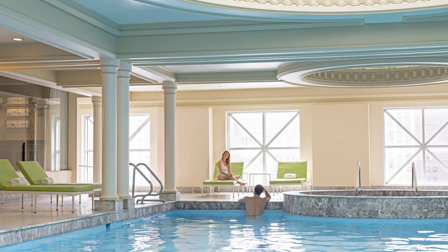 Man at edge in indoor pool looking at woman seated in lime green lounge chair, three more chairs