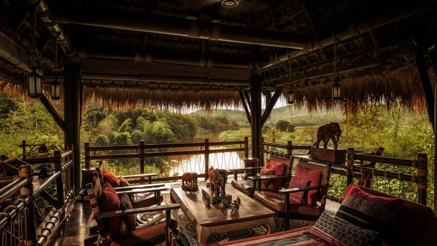 Burma Bar wood tables, chairs with red cushions under thatched-roof cabana