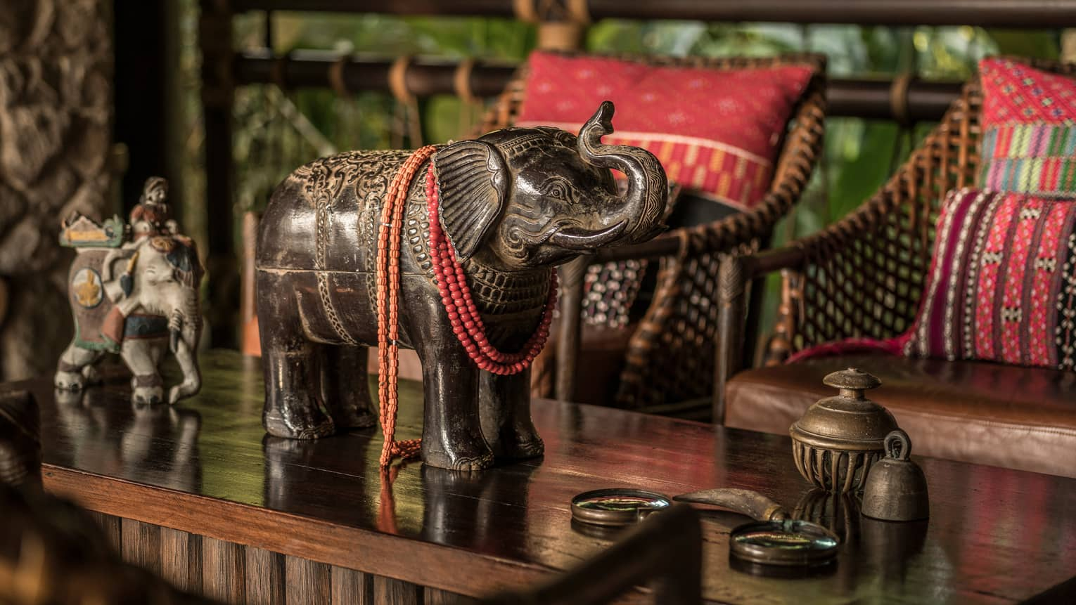 Elephant statue on wood table in front of bamboo sofa with red cushions