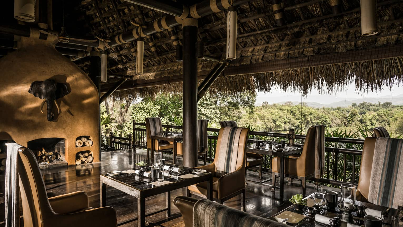Dining tables, leather chairs in wood open-air restaurant under thatched roof