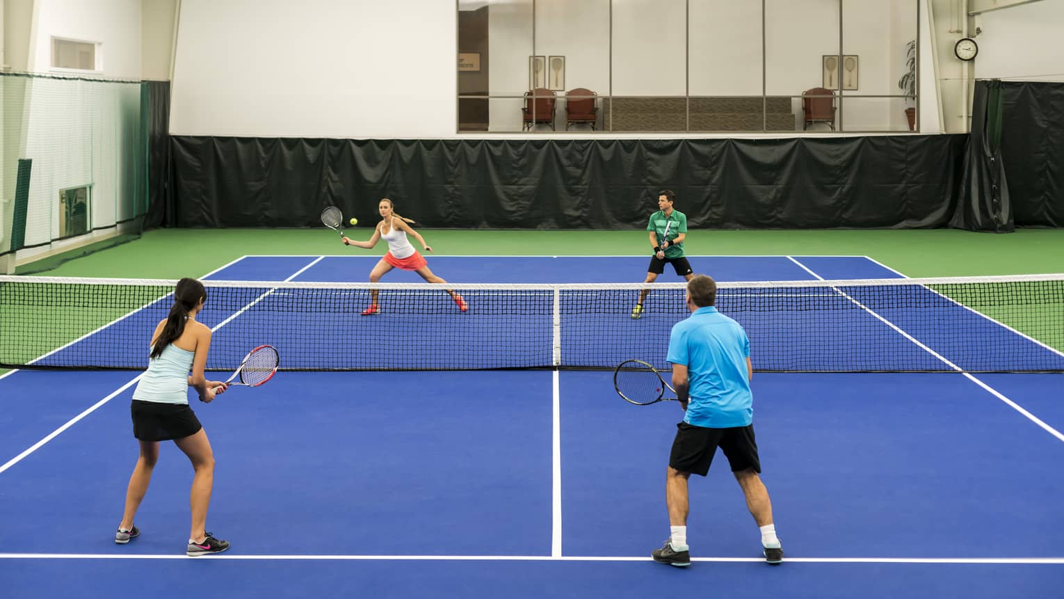 Two women, two men play tennis match on blue court