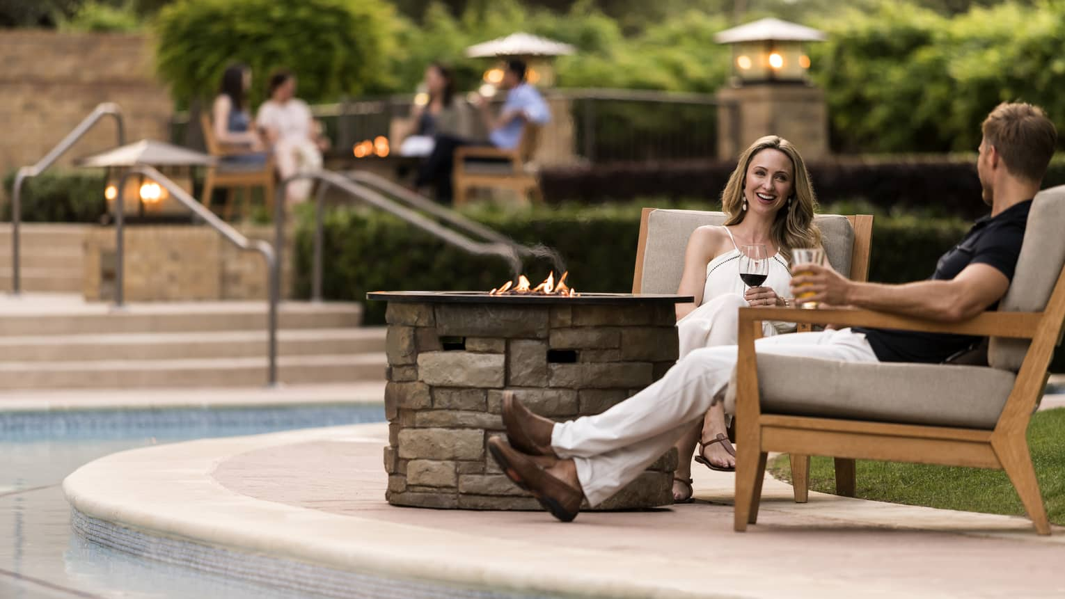 People sitting outside around a fire pit near a pool drinking wine.