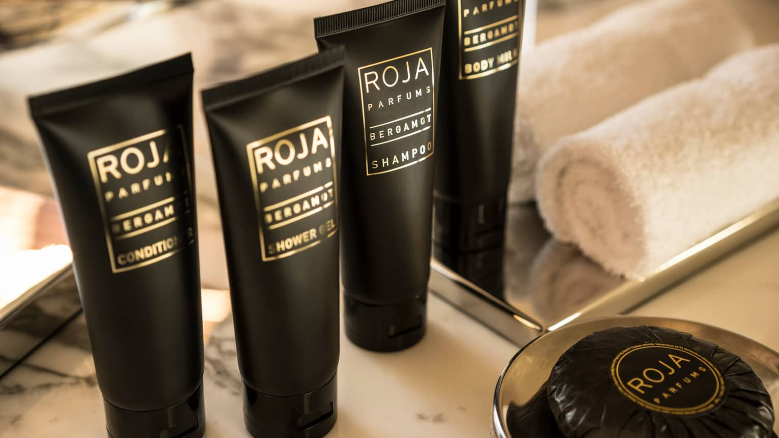 Foru small black bottles with ROJA Parfums gold lettering, toiletry shower gels, soaps