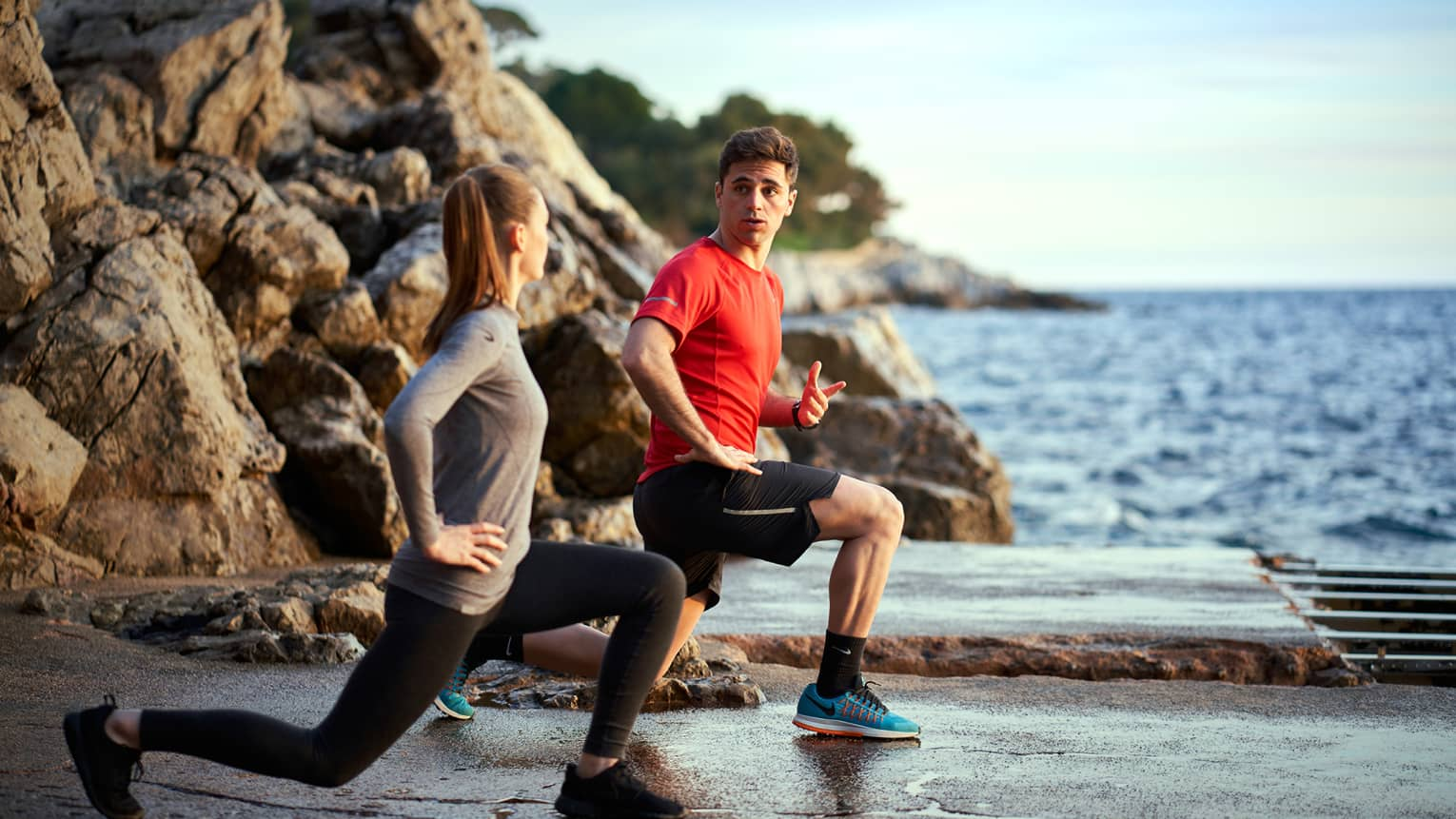 A man trains a woman while doing lunges outside next to the sea and rocks
