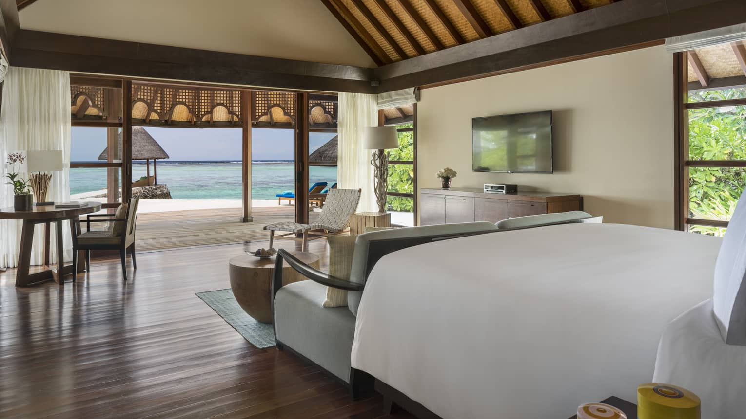 Oceanside bungalow room with wooden furniture and white bedding opening up to ocean