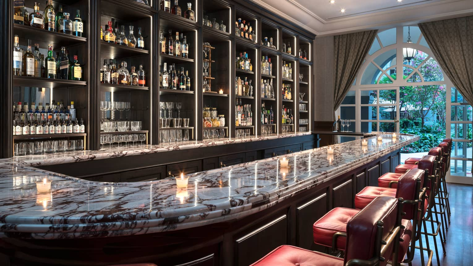 Fifty Mils curved marble bar top with candles, liquor on shelves, arched windows