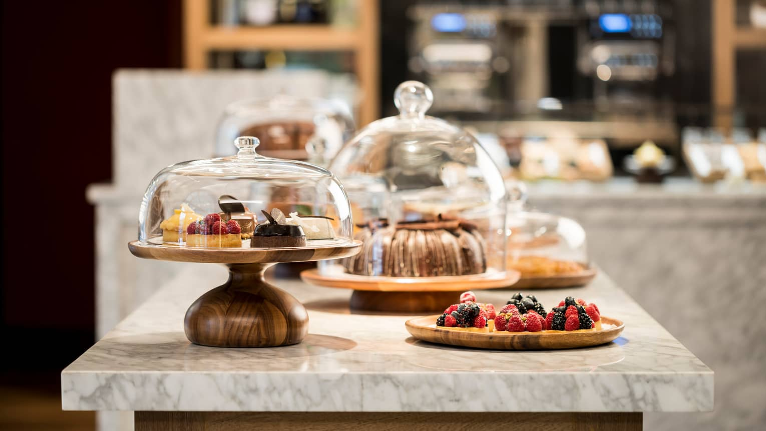 Sweets, desserts and pastries in glass cake displays on Pan Dulce white marble counter