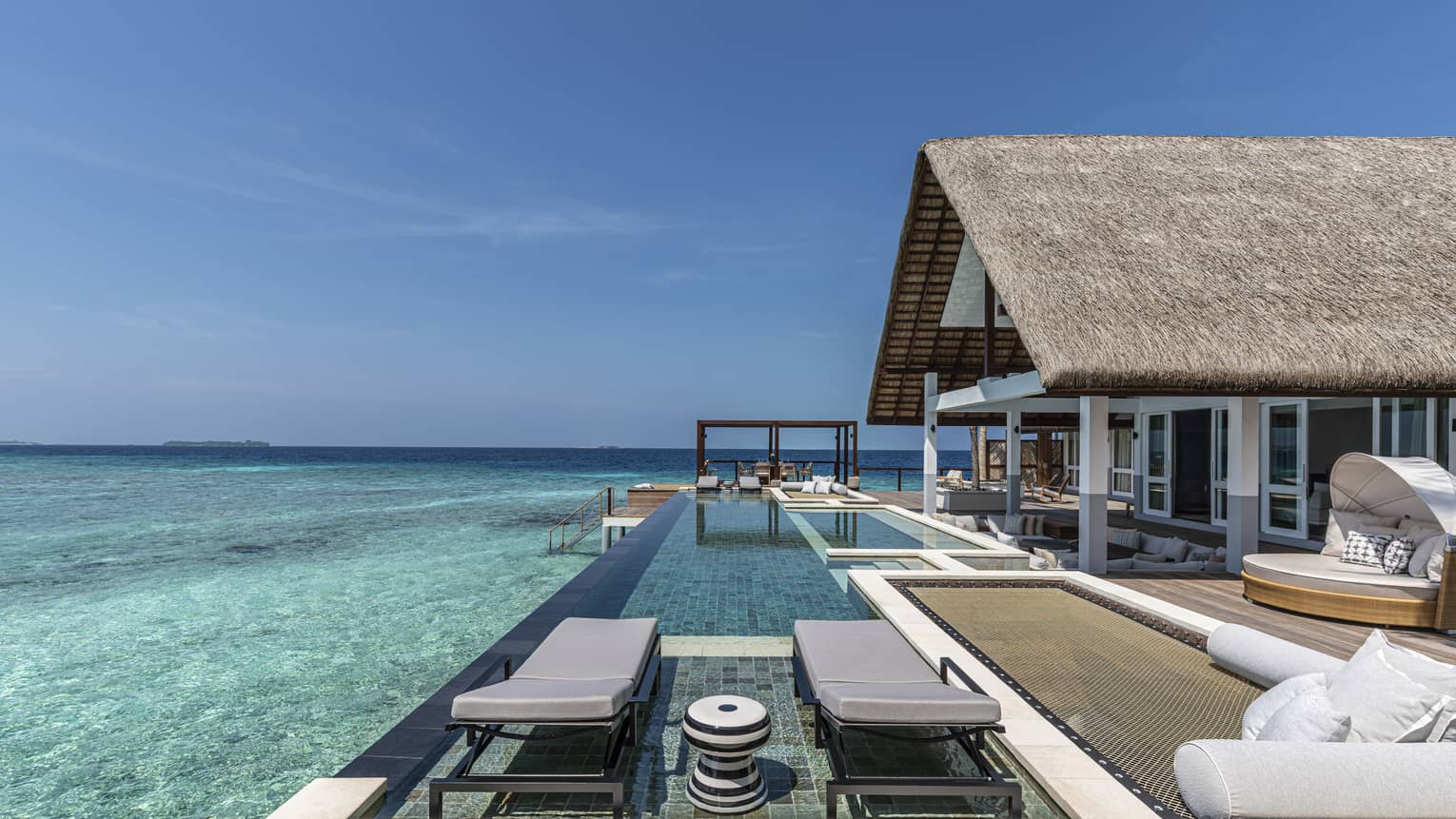 Modern overwater bungalow's expansive deck, with two chaise lounges and infinity pool