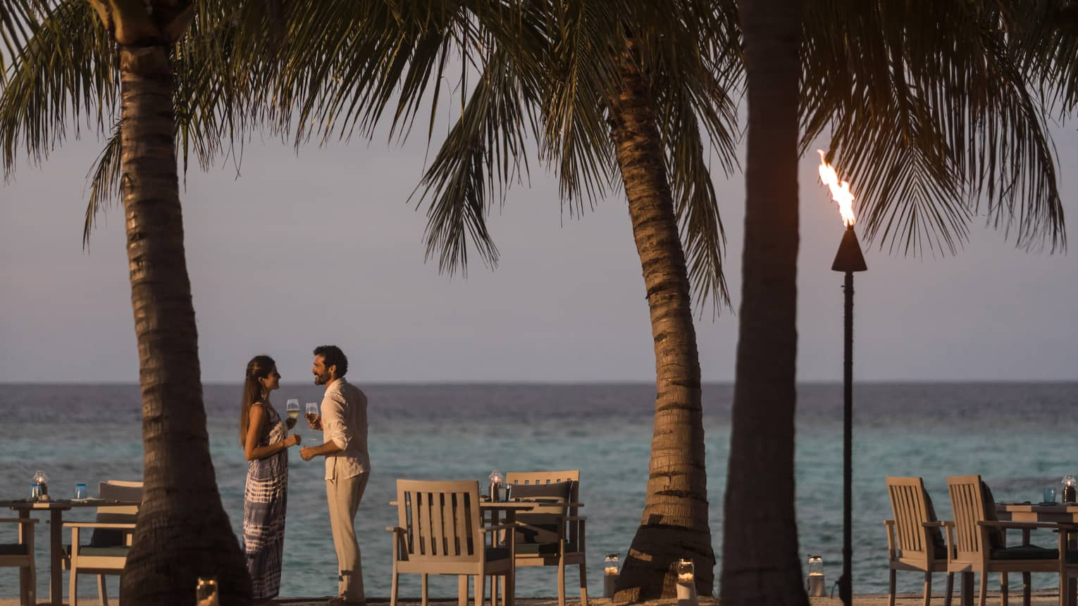 A couple talks on the beach at sunset, a tiki torch burns, table and chairs sit on beach