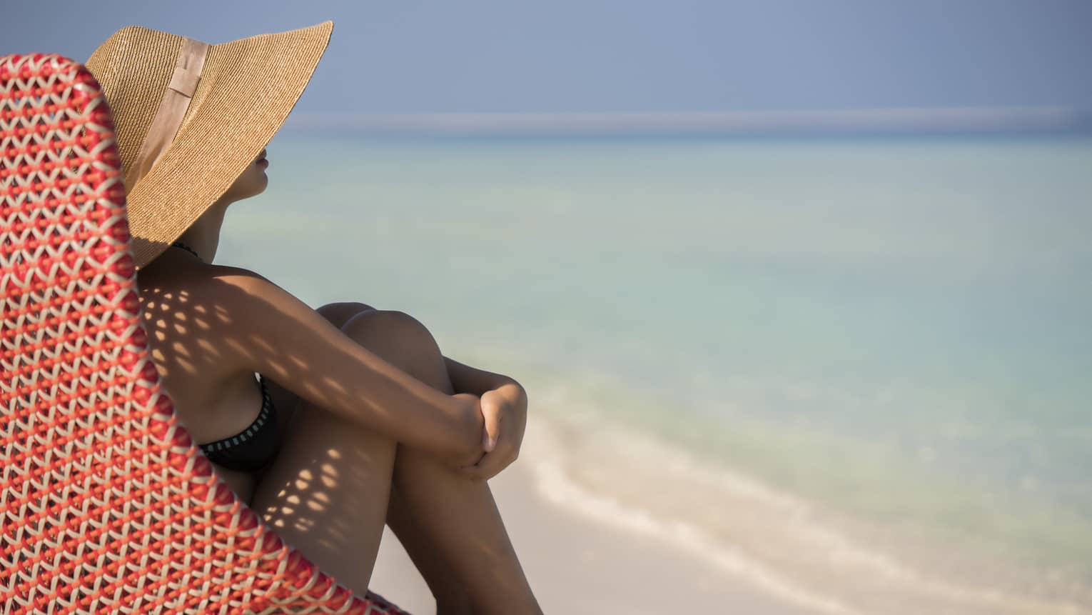 Side of woman wearing sunhat sitting in red wicker beach chair