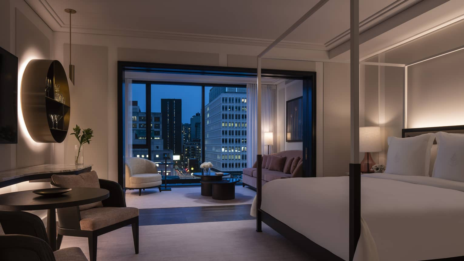Four Seasons Executive Suite, dimly lit with four-poster modern bed and evening patio views
