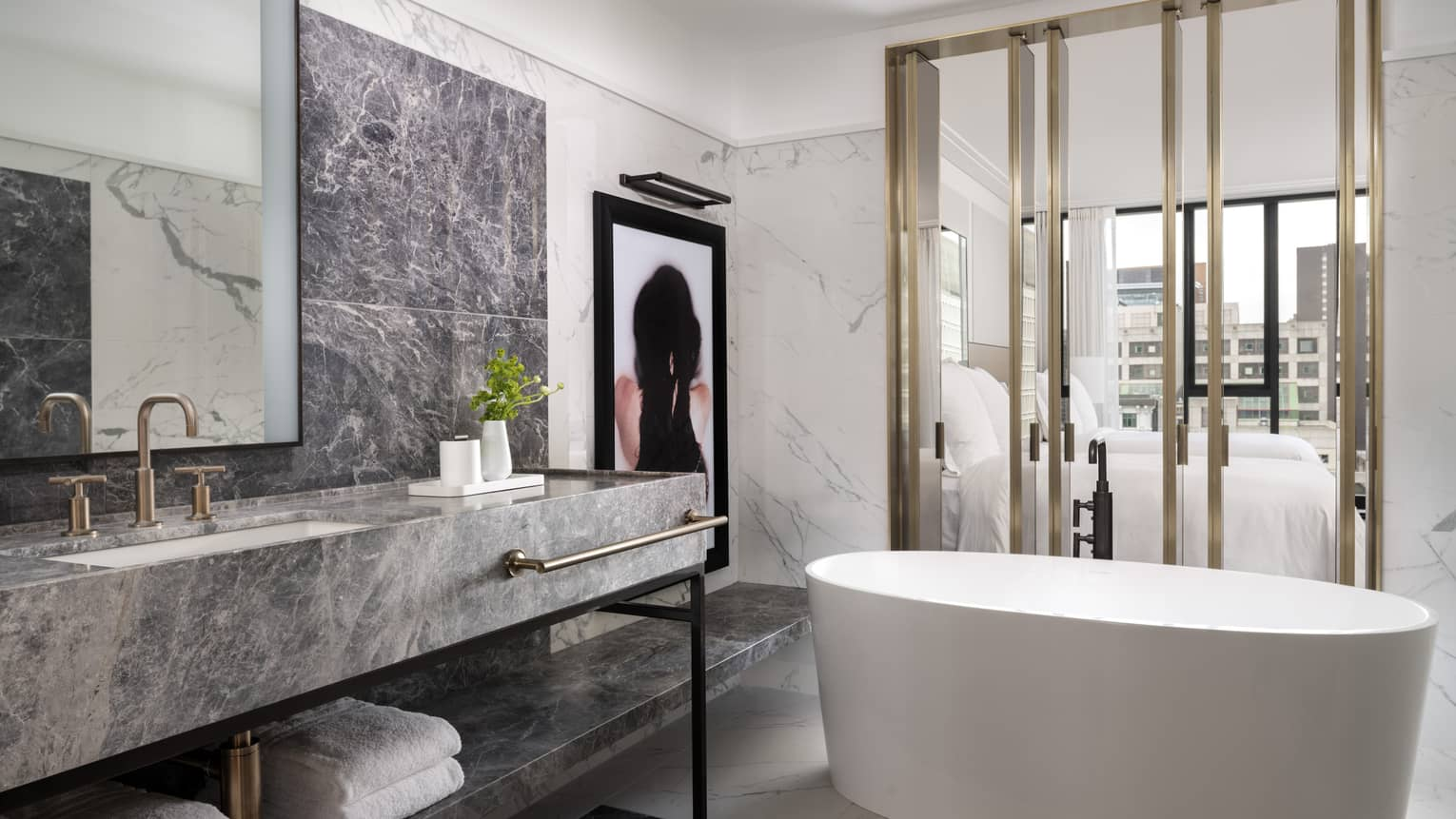 Spa-like guest bathroom with large white soaker tub, grey marbled vanity, modern artwork