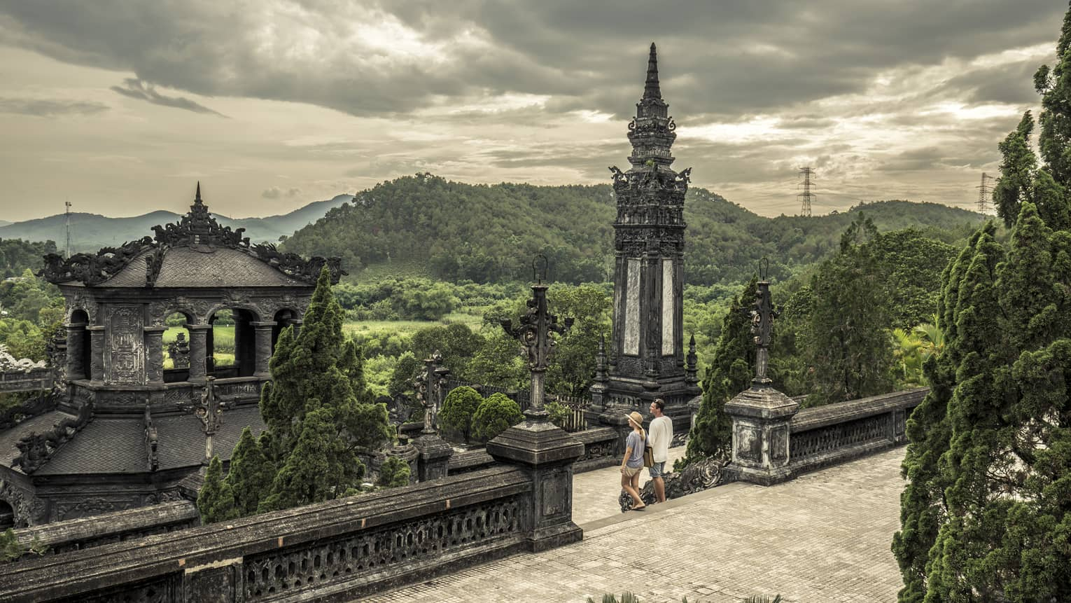 Man and woman walk down steps of historic Imperial City of Hue with stone towers, rolling hills