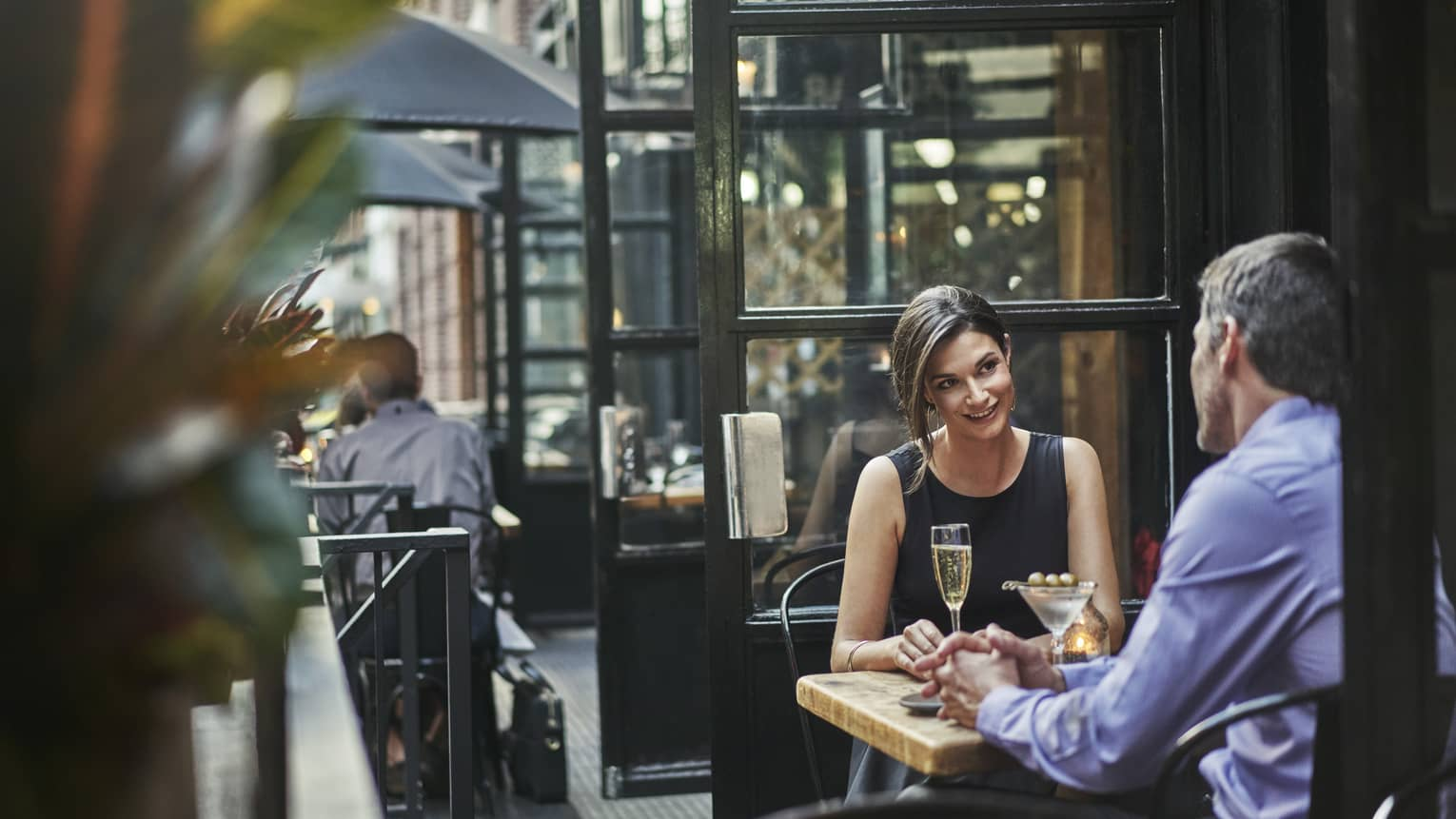 Couple enjoys cocktails at table on streetside patio