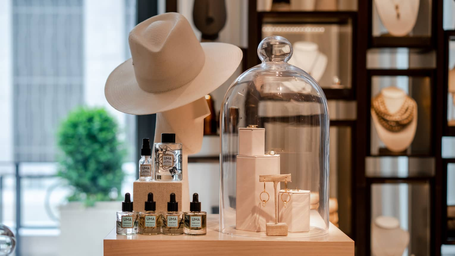 A boutique display of gold jewelry, a beige wide-brimmed hat, and wellness skin care products