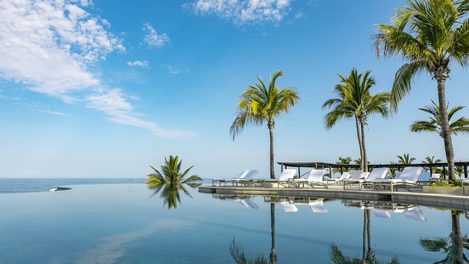 A calm infinity pool reflects the blue sky, clouds and palm trees