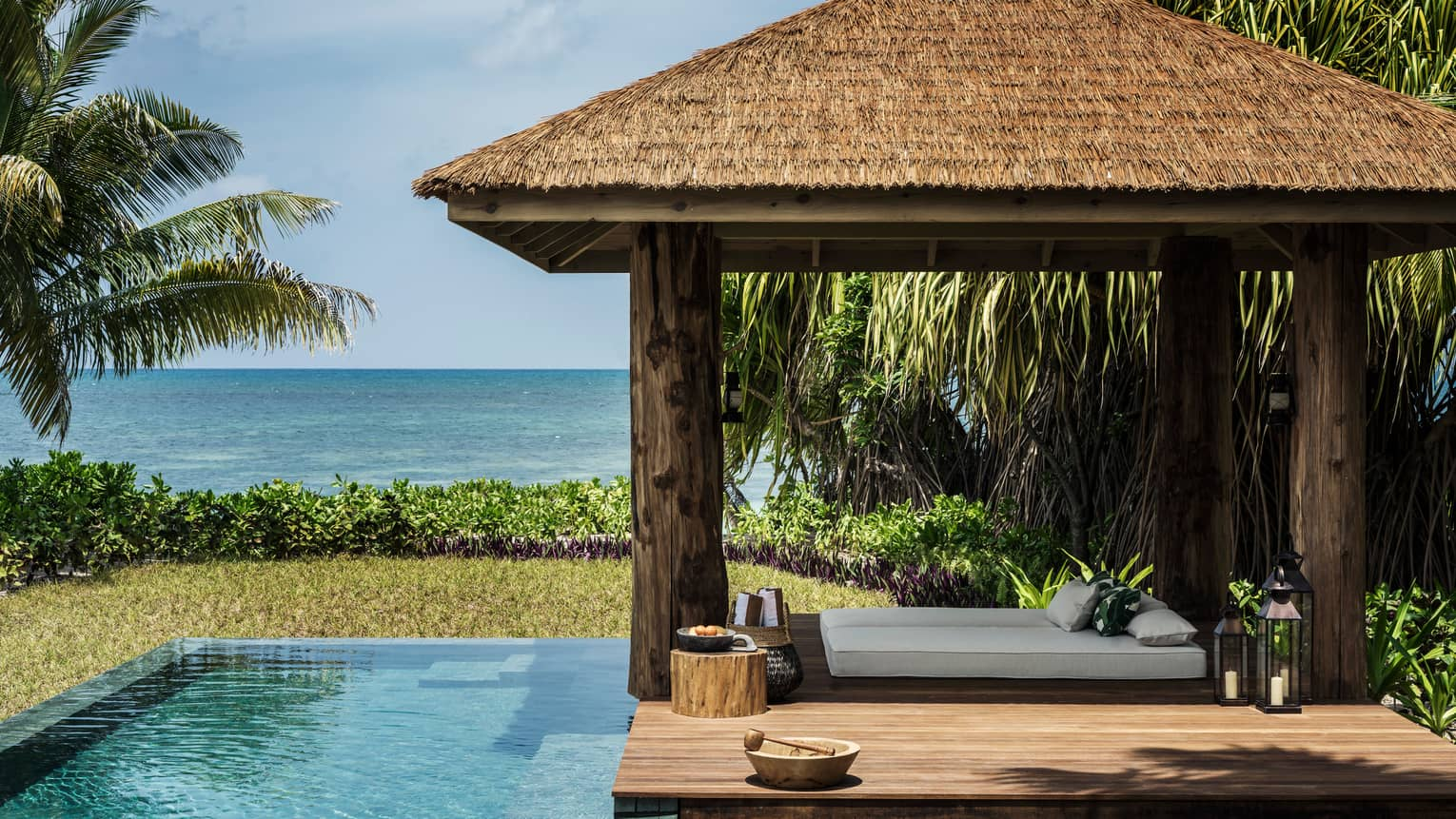 Four-pillar wooden cabana and infinity edge pool, sea in the distance