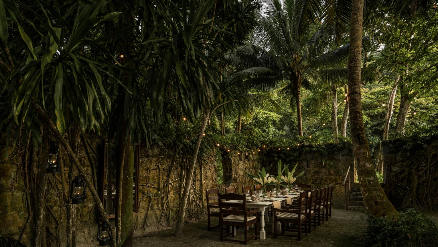 Long dining table with chairs outdoor under palm leaves, near the Foumba Creole ruins at Kannel restaurant