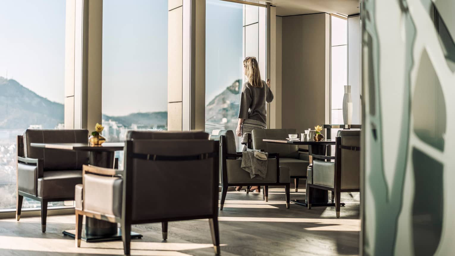 Woman stands at sunny floor-to-ceiling window and looks out at view, near lounge tables, chairs
