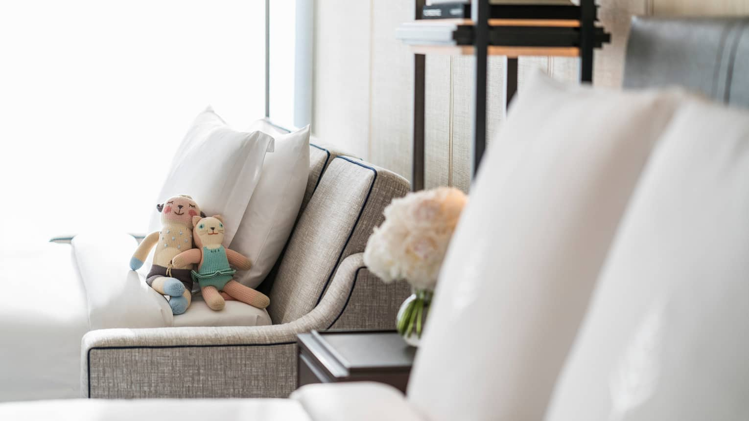 Two small stuffed toys rest against pillows on pull-out sofa beside hotel bed