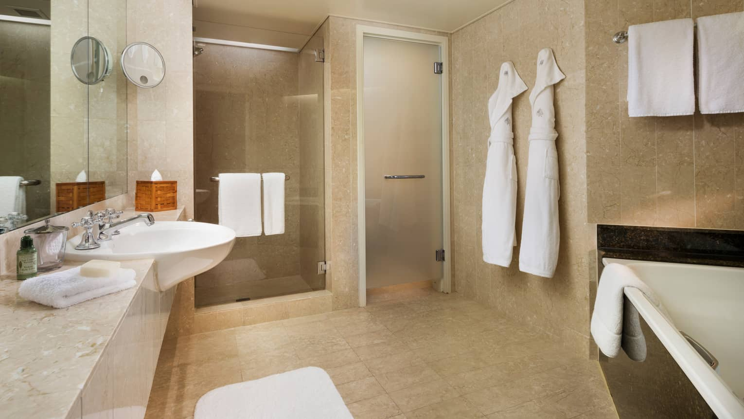 Hotel Suite Full Marble Bathroom Two White Robes Hang By Glass Walk In Showers