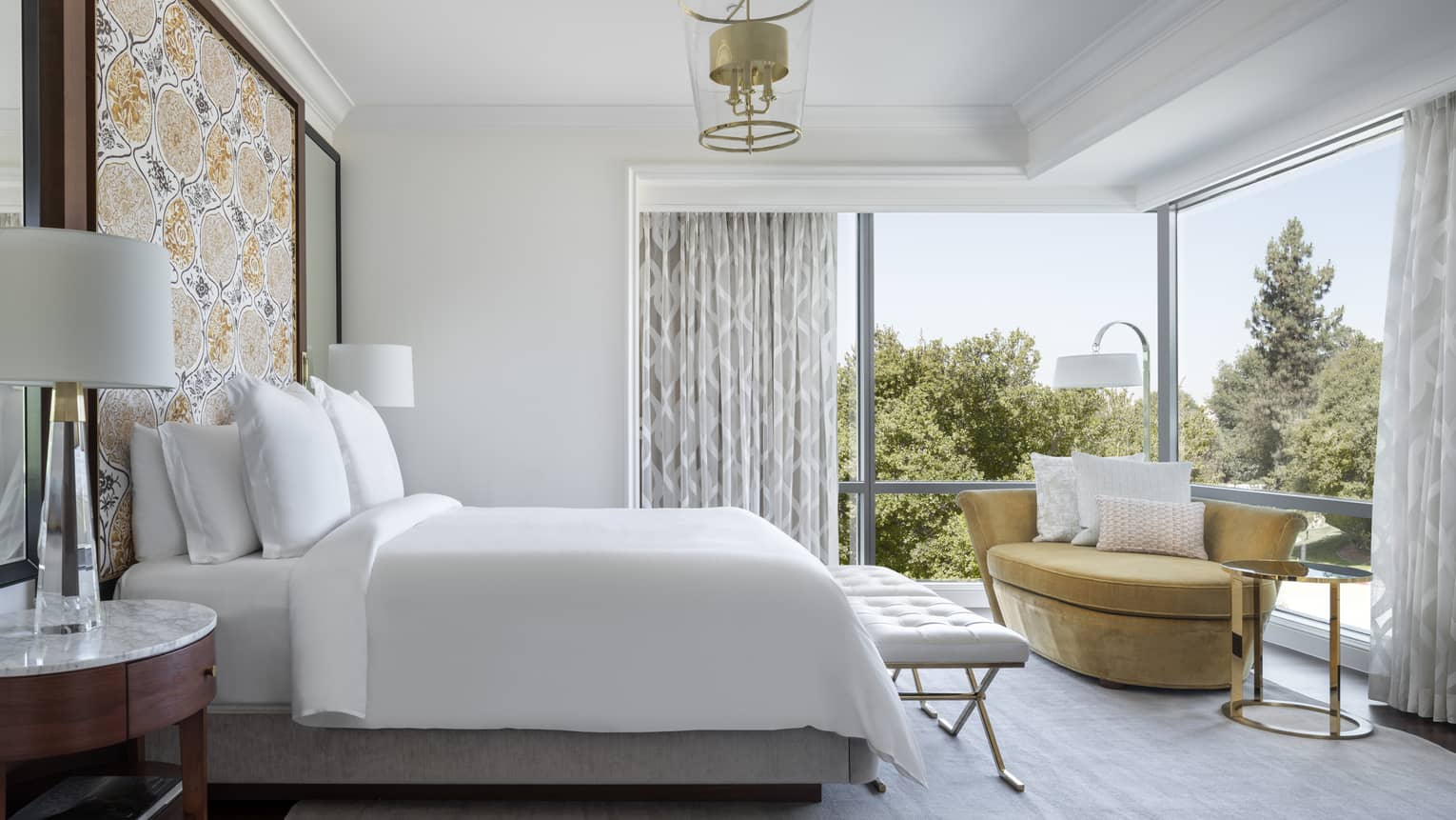 The bed and loveseat of a Malibu Corner One-Bedroom Suite.