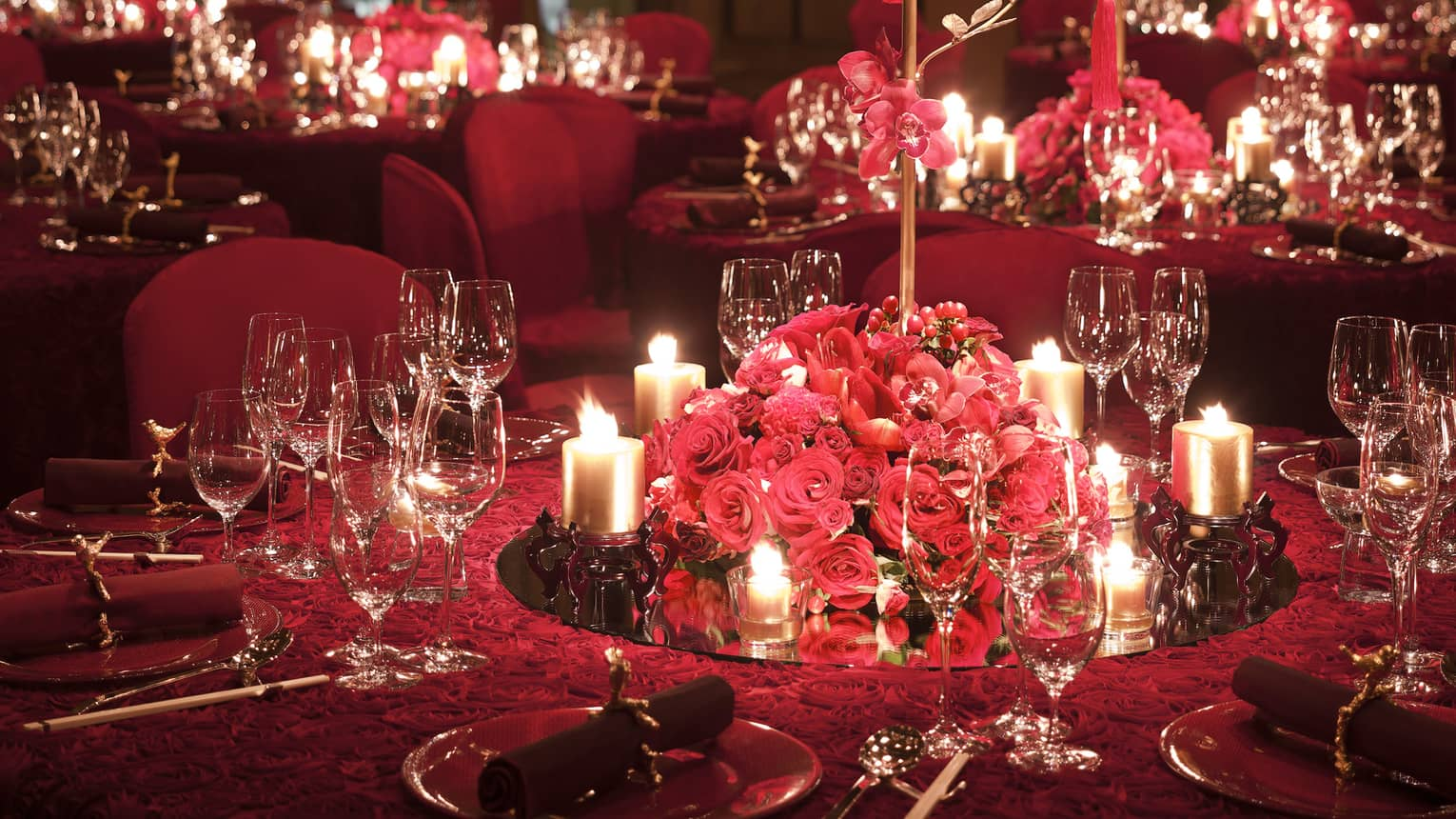 Glowing candles and red roses on gold tree centrepieces on elegant banquet tables