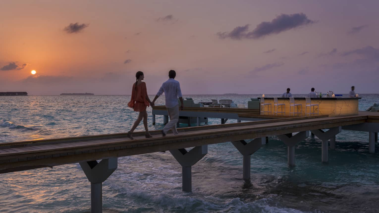 Couple holds hands, walks on wood path over water to Seabar outdoor bar and lounge